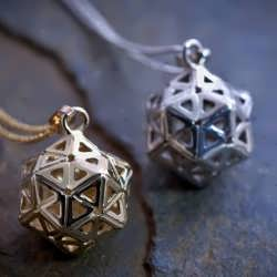 A small silver and gold Consciousness Grid pendants
