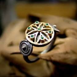 "A gold and oxidized silver ""KA"" ring set with emeralds"