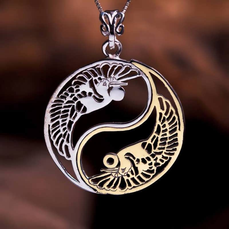 A silver and gold Yin Yang pendant